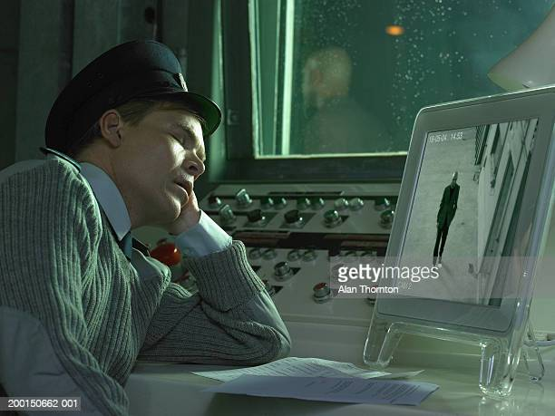 Security guard asleep in front of monitor displaying man