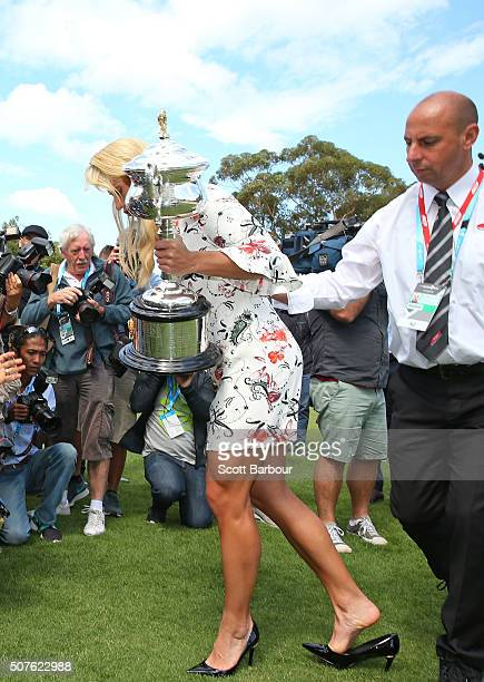 A security guard assists as the high heeled shoe of Angelique Kerber of Germany becomes stuck in the lawn as she holds the Daphne Akhurst Memorial...