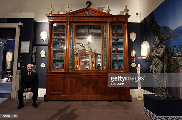 A security guard at Sotheby's auction house sits adjacent to a breakfront bookcase by Karl Roos included in the forthcoming sale of furniture and...