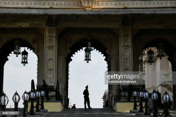 A security guard at the city palace museum stands guard at the museum entry in Udaipur on April 14 2018 / AFP PHOTO / CHANDAN KHANNA