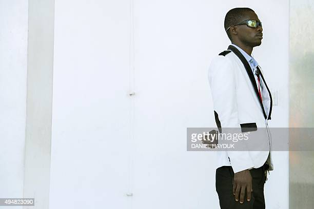 A security guard at the opposition party Chadema headquarters stands guard as opposition party Chadema presidential candidate Edward Lowassa speaks...