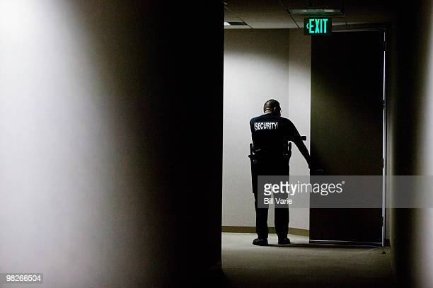 security guard checking hallways - defending stock pictures, royalty-free photos & images