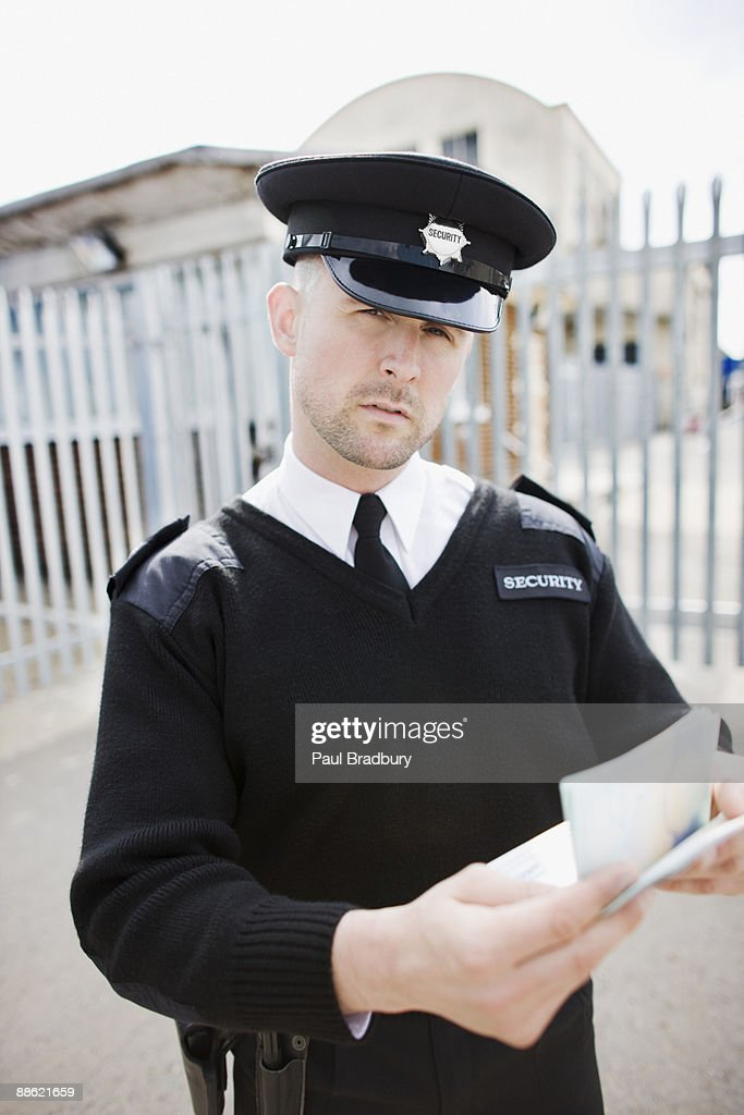 Security guard checking passport : Stock Photo