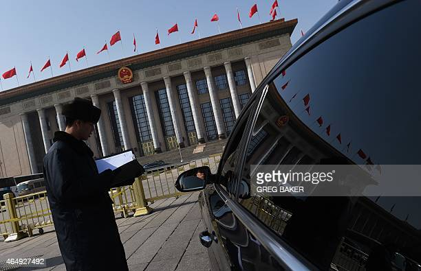 A security guard checks a car entering the courtyard of the Great Hall of the People in Beijing during a meeting on March 2 2015 The Great Hall of...