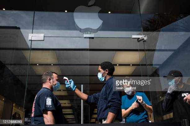 A security guard checks a customers temperature outside the Apple Store on May 13 2020 in Charleston South Carolina Customers had temperatures taken...