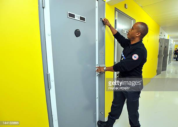 A security guard checks the door lock of a cell in the Nantes new penitentiary located in Carquefou a Nantes suburb western France on May 10 2012 The...