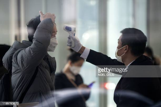 A security guard checks the temperature of an employee inside an office building in Shanghai on February 10 2020 Millions of people in China were...