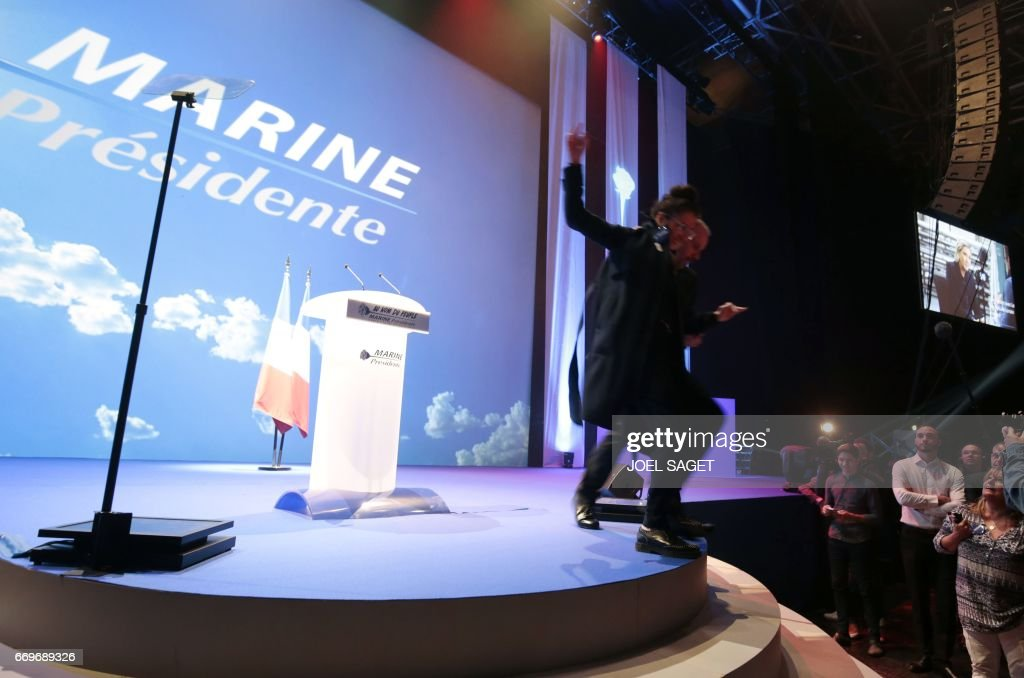 A security guard clears a woman from the stage ahead of the meeting of the French presidential election candidate for the far-right Front National (FN) party, Marine Le Pen, in Paris on April 17, 2017. / AFP PHOTO / joel SAGET