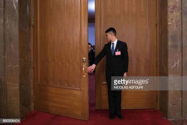 TOPSHOT A security guard closes a door as the parliament votes during the National People's Congress at the the Great Hall of the People in Beijing...