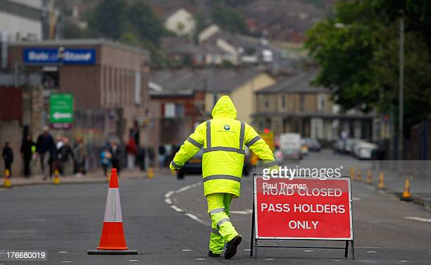 A security guard closes the road before the Sky Bet Championship match between Burnley and Yeovil Town at Turf Moor on August 17 2013 in Burnley...