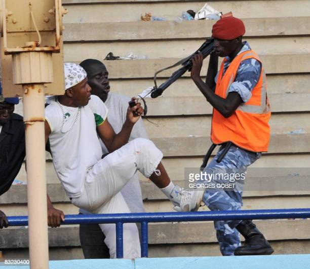 A security guard confronts Senegalese suporters who discontented with the performance of their team caused violent incidents in the stands of the...