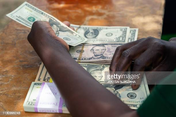 Security guard counts small denominations of USD money on March 14 2019, in the Mutoko rural area of Zimbabwe. - Eastern Zimbabwe receives help to...