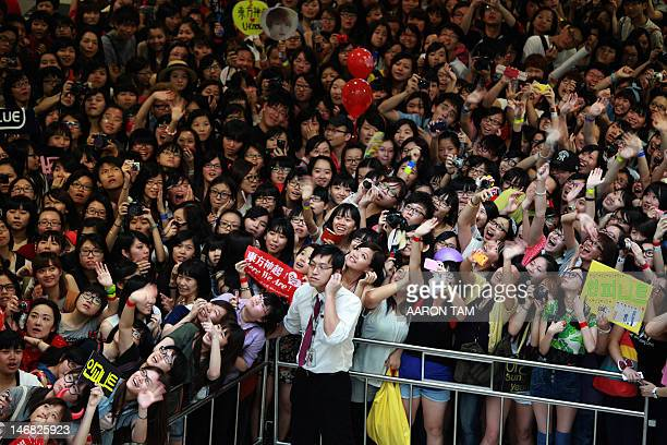 A security guard covers his ears as KPop fans holding signs with the names of their favourite KPop groups cheer and shout outside the venue of the...