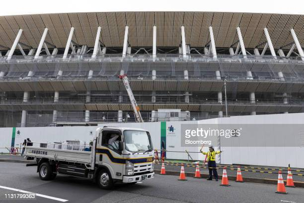 A security guard directs a truck near the construction site of the New National Stadium the main venue for the Tokyo 2020 Olympic and Paralympic...