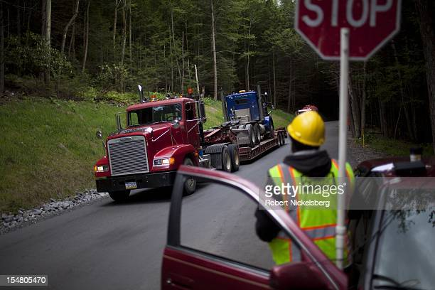A security guard directs oneway traffic of 18wheel tractor trailers September 8 2012 which service the oil and gas drilling operations in Waterville...