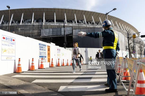 A security guard directs pedestrians crossing a road near the construction site of the New National Stadium the main venue for the Tokyo 2020 Olympic...