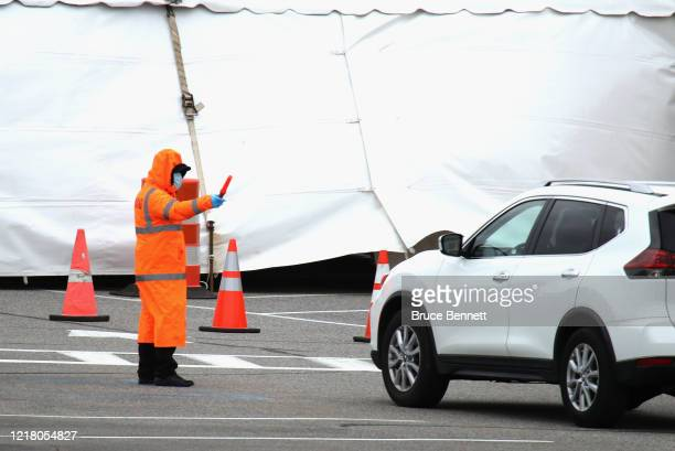 Security guard directs traffic at a drive-in COVID-19 test site at Huntington High School on April 10, 2020 in Huntington, New York. According to...
