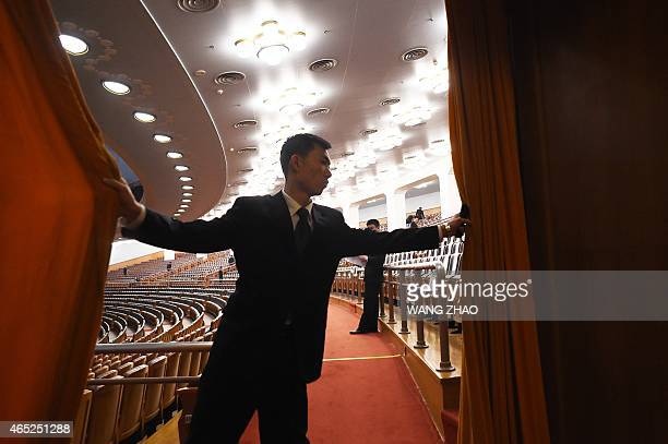 A security guard draws the curtain after the opening session of the National People's Congress in Beijing on March 5 2015 China's Communist...