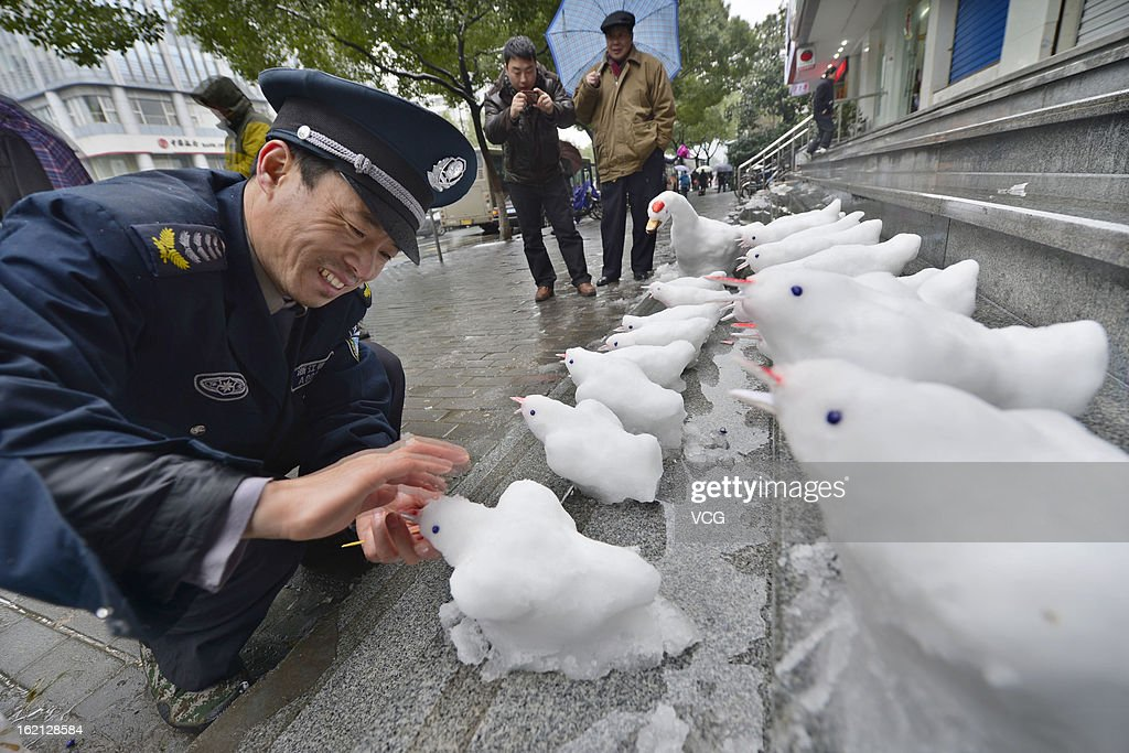 Security guard Du Jinqian makes snow birds on the steps in front of a bank where he works on February 19, 2013 in Hangzhou, China. Heavy snow hit large areas of east China on Tuesday.