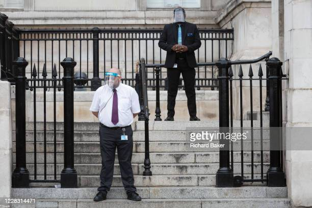 Security guard employees wearing face shields at the National Gallery stand at the bottom of steps leading into a small entrance of the National...