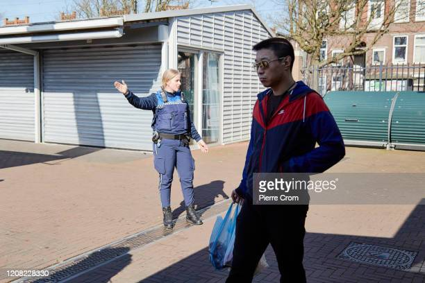 A security guard evacuates The Hague market one of the largest market in Europe amid the worsening COVID19 virus pandemic on March 25 2020 in The...