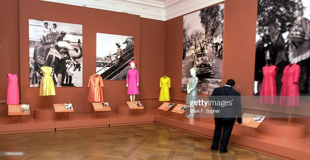A security guard examines some of Jacqueline Kennedy's personal articles which are on display, as well as examples of when such a dress was worn and the history behind it, at the Corcoran Gallery of Art's 'Jacqueline Kennedy: The White House Years' exhibit.
