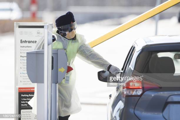 Security guard hands a person a parking pass as they enter a hospital with a coronavirus assessment center in Mississauga, Ontario, Canada, on...