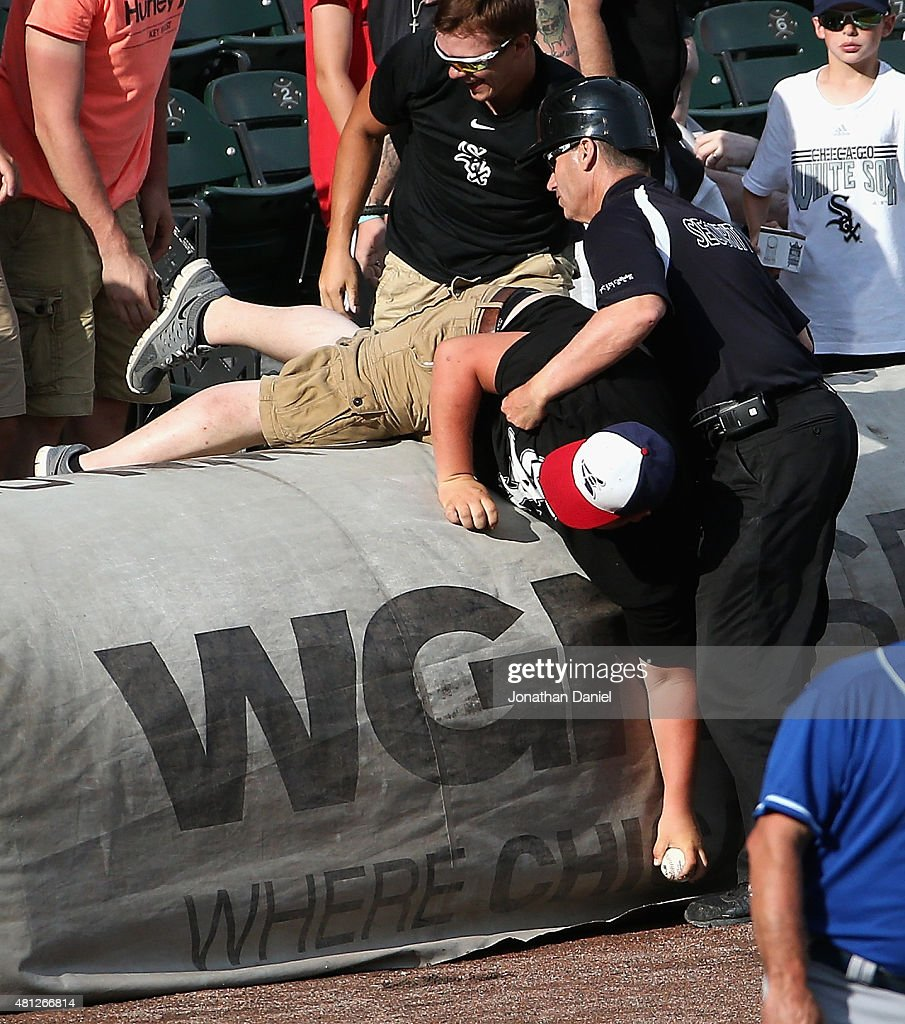 A security guard helps a fan back over the tarp after he fell over grabbing a foul ball during a game between the Chicago White Sox and the Kansas City Royals at U.S. Cellular Field on July 18, 2015 in Chicago, Illinois. The Royals defeated the White Sox 7-6 in 13 innings.
