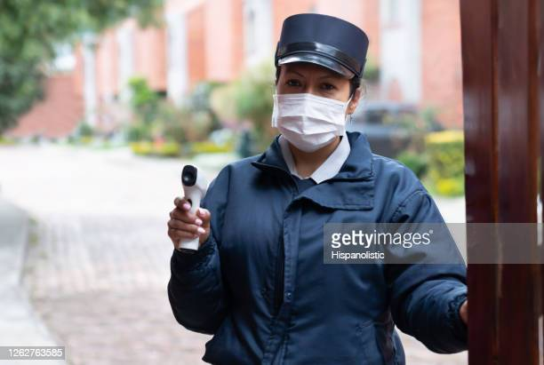 security guard holding an infrared thermometer to check people's temperature - biosecurity stock pictures, royalty-free photos & images