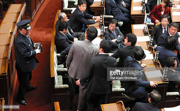 A security guard holds a shoe thrown in while Upper House lawmakers look back the direction before the vote for the state secrets protection bill at...