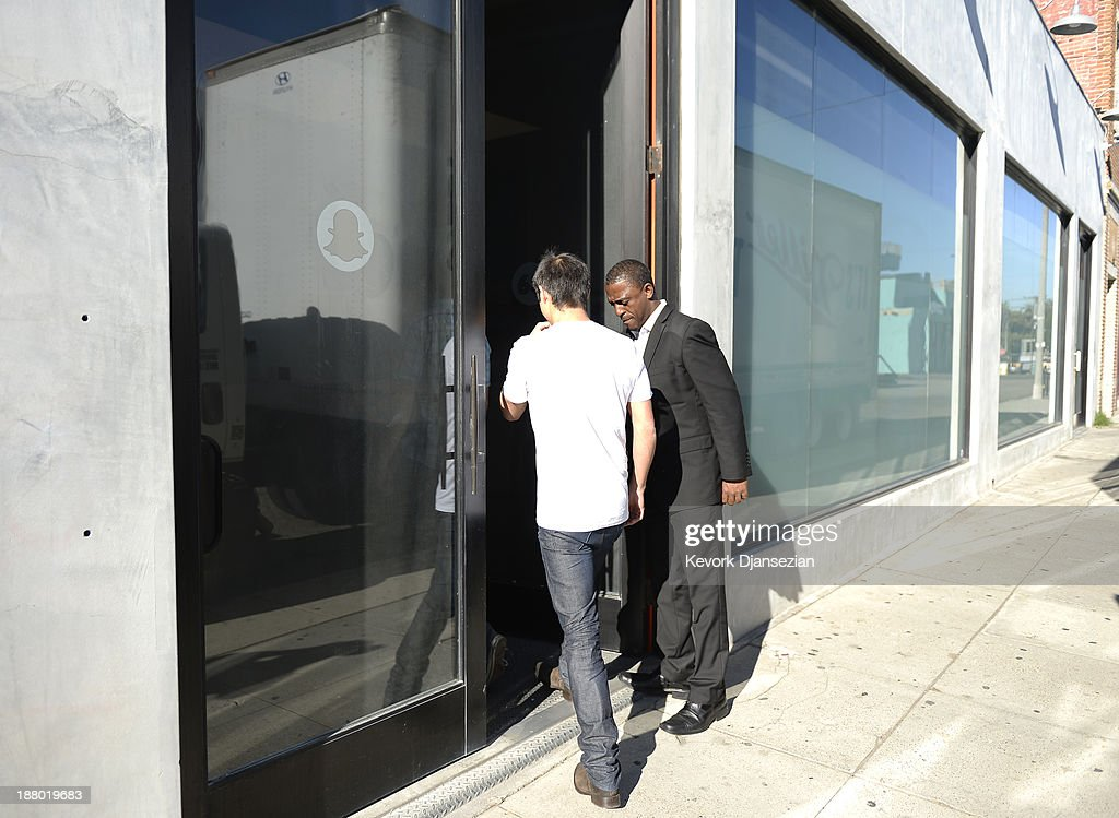 A security guard holds the door for a man to enter the new headquarters of Snapchat November 14, 2013 in Venice, California. Snapchat recently turned down a $3-billion buyout offer from Facebook.