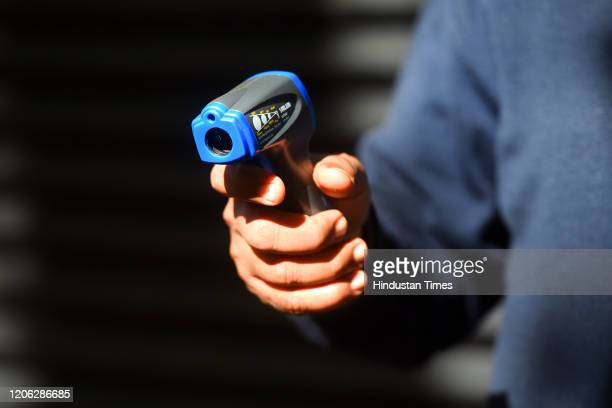 Security guard holds up an infrared thermometer used to screen people as a precautionary measure against coronavirus , at Barakhamba Road on March 9,...