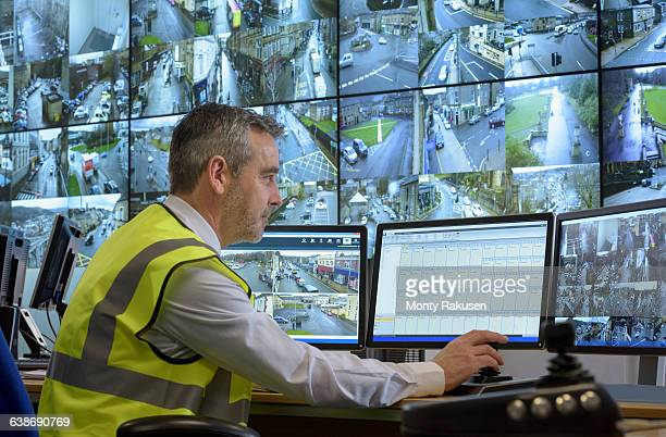 Security guard in security control room with video wall