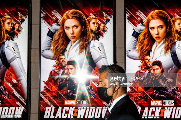 Security guard inside the lobby of the El Capitan Theatre, in Hollywood, CA, with posters on display for Marvel Studios Black Widow, opening weekend,...