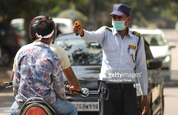 Security guard is seen screening visitors outside the DLF phase-2 entry gate, during the first day of the nationwide lockdown due to coronaviurs, at...