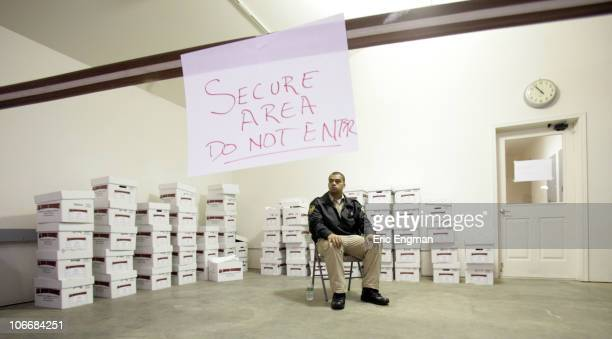 A security guard keeps a watchful eye over boxes of ballots as the State of Alaska Division of Elections tally the writein ballots November 10 2010...