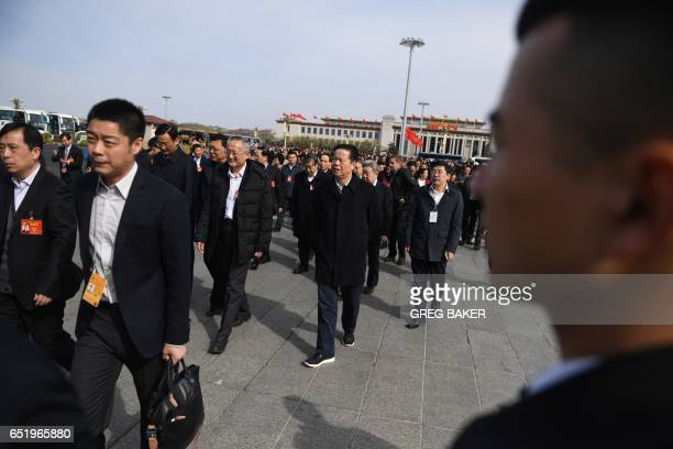 A security guard keeps watch as delegates arrive before a plenary session of the Chinese People's Political Consultative Conference at the Great Hall...