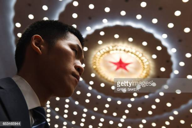 A security guard keeps watch as delegates file out after the closing session of the National People's Congress China's legislature in Beijing's Great...