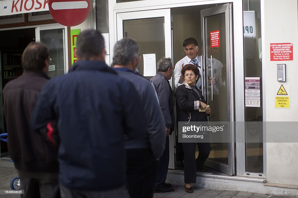 A security guard lets a customer exit a branch of a Cyprus Popular Bank Pcl, also known as Laiki Bank, as other customers wait their turn to enter, in Nicosia, Cyprus, on Friday, March 29, 2013. Cypriots face a second day of bank controls over their use of the euro as officials in Europe urged the country to move quickly to lift the restrictions, the first time they have been imposed on the common currency. Photographer: Simon Dawson/Bloomberg via Getty Images