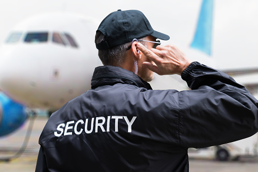 Security Guard Listening To Earpiece Against Building 908827618