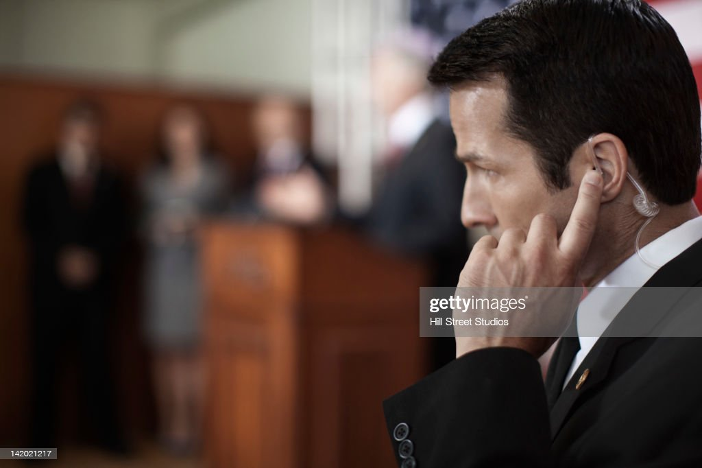 Security guard listening to earpiece at public speech : Stock Photo