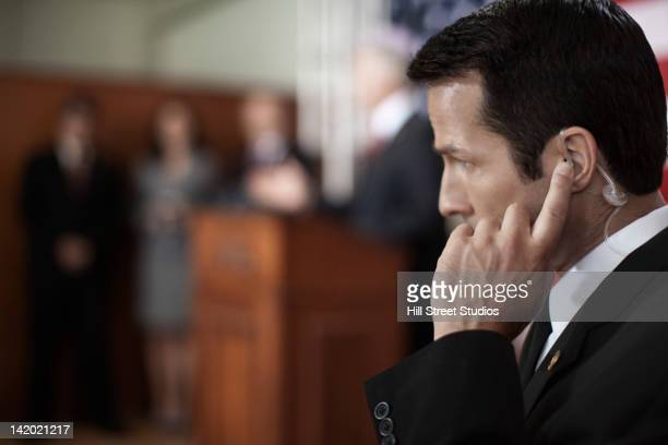 Security guard listening to earpiece at public speech