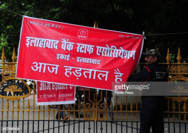 A security guard locks a main gate as Bank workers hold a nationwide strike for their various demands in Allahabad