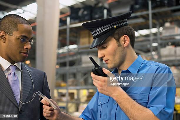 security guard looking at businessman's identification - racismo fotografías e imágenes de stock