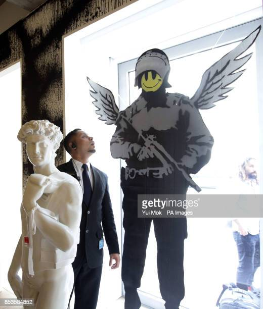 Security guard looking at the artist's work during a press preview for the exhibition Banksy: The Unauthorised Retrospective, curated by Steve...