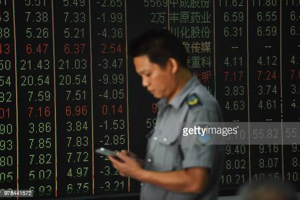 A security guard looks at his mobile phone in front of a screen displaying stock market figures at a securities company in Hangzhou in China's...