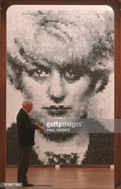 A security guard looks at his watch in front of the controversial painting of British Moors child murderer Myra Hindley 16 September The painting by...