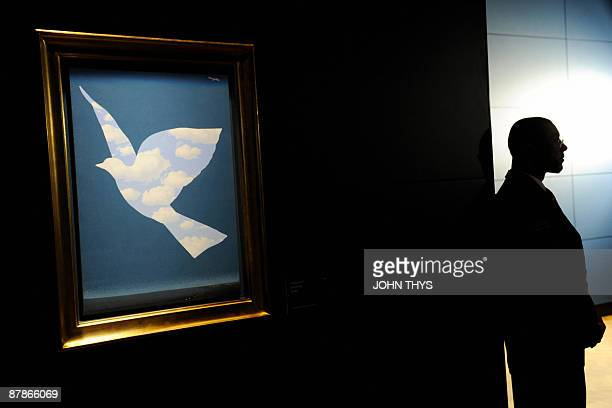 A security guard looks on as he stands beside a painting entitled ' Sky Bird 1966 ' by the Belgian artiste Rene Magritte at the press opening of the...