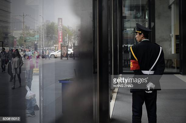 A security guard looks out at the entrance of a mall in Beijing on April 13 2016 China's growth slowed further in the first three months of this year...