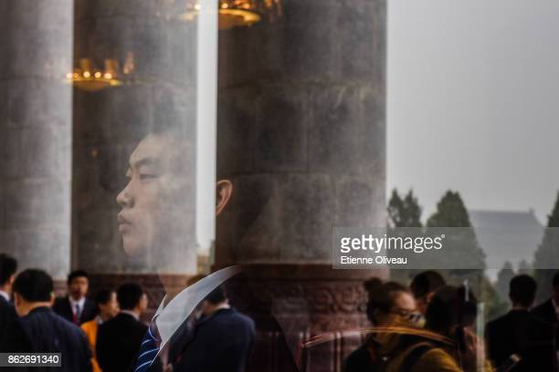 A security guard looks out from a window of the Great Hall of the People during the opening session of the 19th Communist Party Congress held at the...